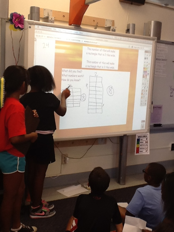 During math, two girls were teaching one another about their strategies on the ActivBoard.