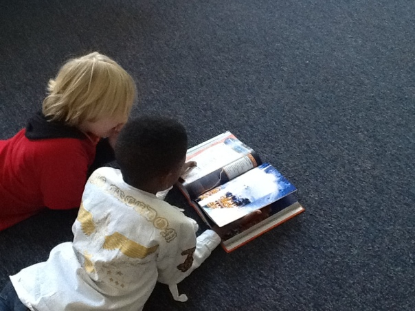 Here are two scientists exploring and discussing a science textbook in our room.