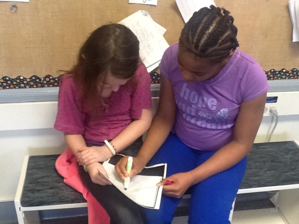 Nataiya and Cheyenne are also reading the text closely in order to find the thesis and supporting evidence.