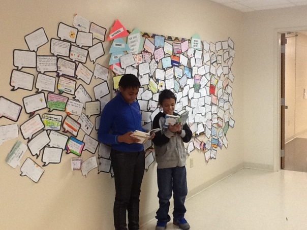Another posed picture, but Nataiya and Malakai look like they are happily reading in front of the OODLES of quotes that students wrote this week about how the library helps them.