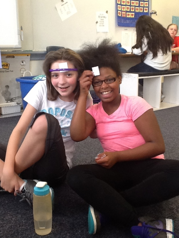 Look at how fun math can be!  We played a game, similar to Headbandz, where kids had to ask yes or no questions about the shape on their head and then they had to guess the shape based on the responses to their questions.