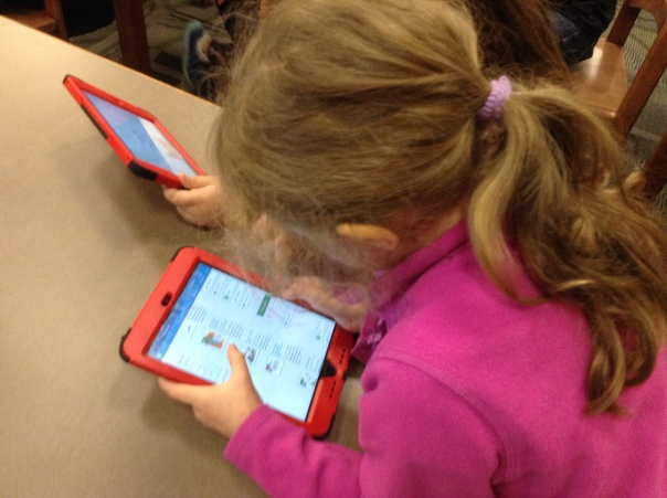 Look at this first grader as she practices reading and checking our eBooks from the Robinson Library.