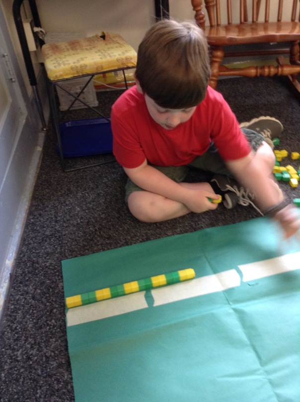 Wyatt measured a poster with unifiix cubes.