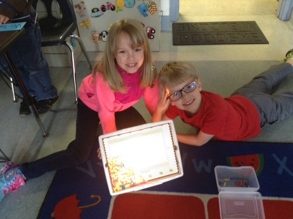 Emily and Alec are quite proud of their Lite Brite creation, as you can tell from their smiling faces!