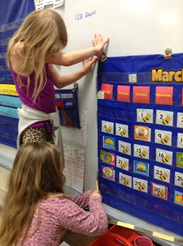 Olivia and Quinn worked to measure our classroom calendar with their measuring strips.