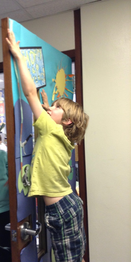 Ethan worked to measure our classroom door with his measuring strip.