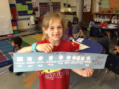 Gray is quite happy to share her math work about our day!