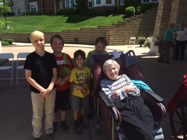 Here are some children posing for a photo with a resident after talking with her.